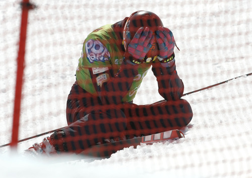 Rick Egan  | The Salt Lake Tribune   Trevor Ricioli (green) hangs his head after crashing through the fence in race six, in the Men's Ski Cross at the Canyons, Friday, March 1, 2013.
