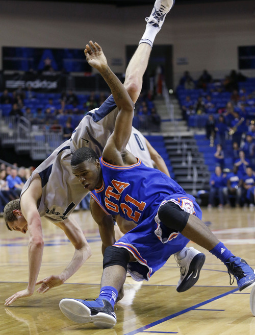 Utah State forward Ben Clifford (1) lands on Texas-Arlington forward Greg Gainey (21) after they jumped for a rebound during the first half of an NCAA college basketball game, Saturday, March 2, 2013, in Arlington, Texas. (AP Photo/LM Otero)