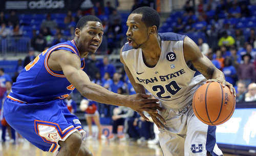 Utah State guard TeNale Roland (20) drives against Texas-Arlington guard Cameron Catlett (25) during the first half of an NCAA basketball game, Saturday, March 2, 2013, in Arlington, Texas. (AP Photo/LM Otero)