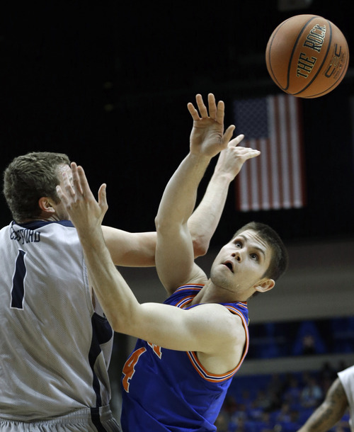 Texas-Arlington guard Drew Charles (4) passes off against Utah State forward Ben Clifford (1) during the first half of an NCAA basketball game Saturday, March 2, 2013, in Arlington, Texas. (AP Photo/LM Otero)