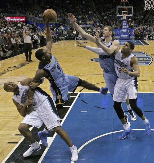 Orlando Magic's Arron Afflalo, lower left, grabs Memphis Grizzlies' Tony Allen (9) by the arm as he goes after a rebound and Grizzlies' Jon Leuer, second from right, and Magic's Tobias Harris (12) go after the ball during the second half of an NBA basketball game, Sunday, March 3, 2013, in Orlando, Fla. Memphis won the game 108-82.(AP Photo/John Raoux)