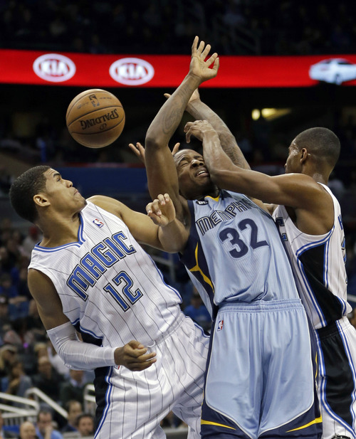 Memphis Grizzlies' Ed Davis (32) gets caught between Orlando Magic's Tobias Harris (12) and Moe Harkless, right, while going up for a rebound during the first half of an NBA basketball game, Sunday, March 3, 2013, in Orlando, Fla. (AP Photo/John Raoux)