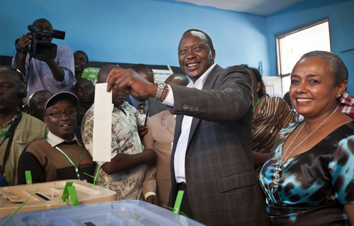 Kenyan Presidential candidate Uhuru Kenyatta casts his vote, accompanied by his wife Margaret Wanjiru Gakuo, right, at the Mutomo primary school near Gatundu, north of Nairobi, in Kenya Monday, March 4, 2013. Five years after more than 1,000 people were killed in election-related violence, Kenyans went to the polls on Monday to begin casting votes in a nationwide election seen as the country's most important - and complicated - in its 50-year history. (AP Photo/Ben Curtis)