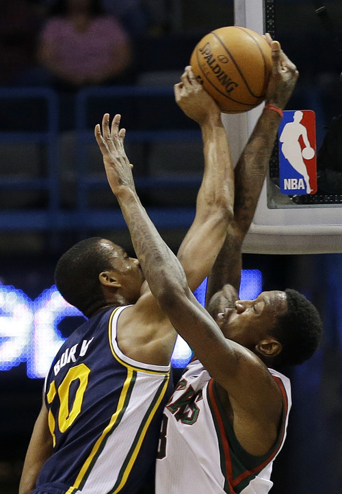 Utah Jazz's Alec Burks, left, shoots against Milwaukee Bucks' Larry Sanders, right, during the first half of an NBA basketball game, Monday, March 4, 2013, in Milwaukee. (AP Photo/Jeffrey Phelps)