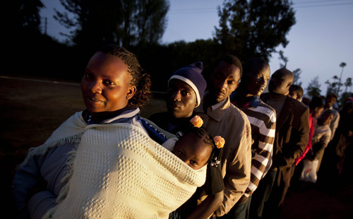 Sarah James Kanaja, left, waits in line with her daughter Silvia, 3, as Kenyans line up to cast their vote in a general election at the Mutomo primary school near Gatundu, north of Nairobi, in Kenya early Monday morning, March 4, 2013. Five years after more than 1,000 people were killed in election-related violence, Kenyans went to the polls on Monday to begin casting votes in a nationwide election seen as the country's most important - and complicated - in its 50-year history. (AP Photo/Ben Curtis)