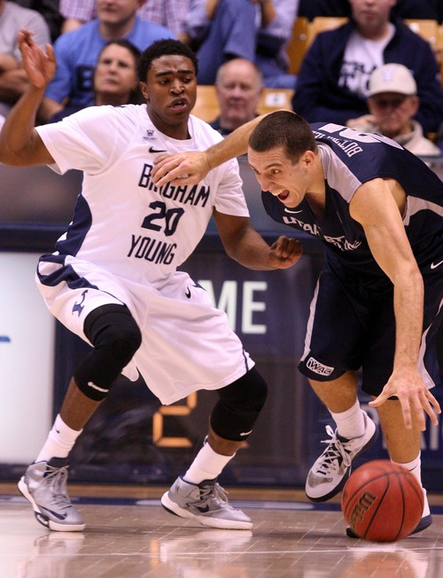 Leah Hogsten  |  The Salt Lake Tribune Brigham Young Cougars guard Anson Winder (20) battles Utah State Aggies guard/forward Spencer Butterfield (21)for possession. Brigham Young University Cougars defeated Utah State University Aggies 70-68 in Provo, February 19, 2013.