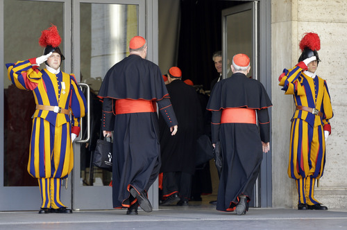 Vatican Swiss guards salute as cardinals arrive for a meeting, at the Vatican, Monday, March 4, 2013. Cardinals from around the world have gathered inside the Vatican for their first round of meetings before the conclave to elect the next pope, amid scandals inside and out of the Vatican and the continued reverberations of Benedict XVI's decision to retire. (AP Photo/Andrew Medichini)