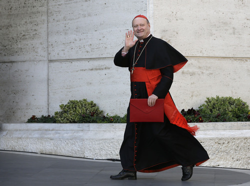 Italian Cardinal Gianfranco Ravasi waves to reporters as he arrives for a meeting, at the Vatican, Monday, March 4, 2013. Cardinals from around the world have gathered inside the Vatican for their first round of meetings before the conclave to elect the next pope, amid scandals inside and out of the Vatican and the continued reverberations of Benedict XVI's decision to retire. (AP Photo/Andrew Medichini)
