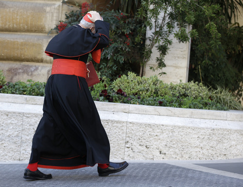 An unidentified cardinal holds his skull cap to prevent it from blowing away in the wind as he arrives for a meeting, at the Vatican, Monday, March 4, 2013. Cardinals from around the world have gathered inside the Vatican for their first round of meetings before the conclave to elect the next pope, amid scandals inside and out of the Vatican and the continued reverberations of Benedict XVI's decision to retire. (AP Photo/Andrew Medichini)