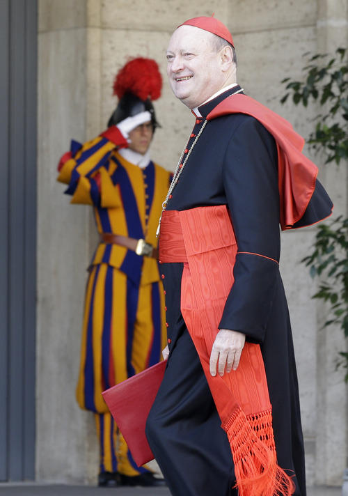 Italian Cardinal Gianfranco Ravasi smiles to reporters as he arrives for a meeting, at the Vatican, Monday, March 4, 2013. Cardinals from around the world have gathered inside the Vatican for their first round of meetings before the conclave to elect the next pope, amid scandals inside and out of the Vatican and the continued reverberations of Benedict XVI's decision to retire. (AP Photo/Andrew Medichini)