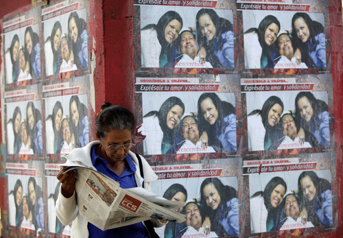 """A woman reads a newspaper as she stands by a wall covered with posters showing Venezuela's President Hugo Chavez pictured with his daughters Maria Gabriela, and Rosa Virginia, outside the military hospital in Caracas, Venezuela, Tuesday, March 5, 2013. A brief statement read on national television by Communications Minister Ernesto Villegas late Monday carried the sobering news about the charismatic 58-year-old leader's deteriorating health. Villegas said Chavez is suffering from """"a new, severe infection."""" The state news agency identified it as respiratory. (AP Photo/Ariana Cubillos)"""