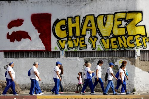 """Pedestrians walks past graffiti that reads in Spanish; """"Chavez lives and will prevail,"""" outside the military hospital in Caracas, Venezuela, Tuesday, March 5, 2013. A brief statement read on national television by Communications Minister Ernesto Villegas late Monday carried the sobering news about the charismatic 58-year-old leader's deteriorating health. Villegas said President Hugo Chavez is suffering from """"a new, severe infection."""" The state news agency identified it as respiratory. (AP Photo/Ariana Cubillos)"""