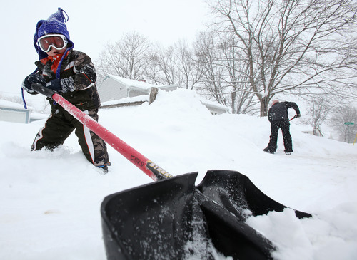 Bill Ford gets help shoveling the sidewalk by his 3-year-old son, Bray, during a winter storm that came through the area in Monona, Wis., Tuesday, March 5, 2013. (AP Photo/Wisconsin State Journal/Amber Arnold)