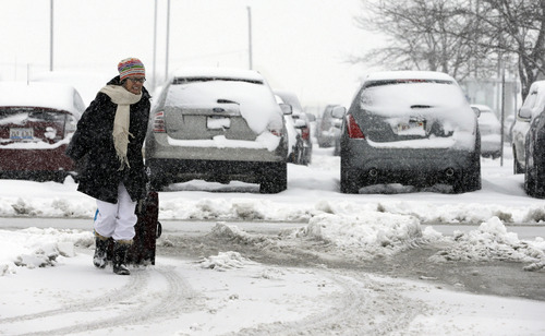 Diana Stewart carries her luggage case in the parking lots O'Hare International Airport in Chicago, Tuesday, March 5, 2013. A late winter storm packing up to 10 inches of snow sent officials in weather-hardened Chicago into action Tuesday to prevent a repeat of scenes from two years ago, when hundreds of people in cars and buses were stranded on the city's marquee thoroughfare during a massive blizzard. (AP Photo/Nam Y. Huh)