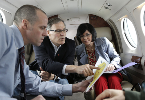 Washington Gov. Jay Inslee, center, is briefed by Dept. of Ecology Director Maia Bellon, right, as Washington State Patrol pilot Scott Sborov, left, looks on, Wednesday, March 6, 2013, in Olympia, Wash., prior to their flight to Richland, Wash. to tour the Hanford Nuclear Reservation and meet with Dept. of Energy officials in order to learn more about tanks on the site that are leaking radioactive waste. (AP Photo/Ted S. Warren)