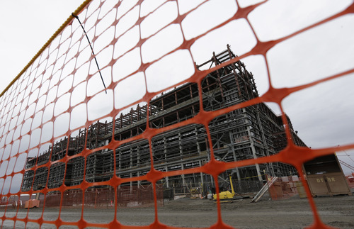 A waste treatment plant under construction is shown behind a plastic fence, Wednesday, March 6, 2013, on the Hanford Nuclear Reservation near Richland, Wash. Work on the  building has been repeatedly delayed due to design and technological setbacks. The project was one of several stops for Washington Gov. Jay Inslee as he toured Hanford Wednesday and met with Dept. of Energy officials in order to learn more about tanks on the site that are leaking radioactive waste. (AP Photo/Ted S. Warren)