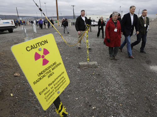 Washington Gov. Jay Inslee, second from right, walks near a sign warning of radiation, Wednesday, March 6, 2013, as he tours the C Tank Farm at Hanford Nuclear Reservation near Richland, Wash. Inslee was at Hanford to meet with Dept. of Energy officials in order to learn more about tanks on the site that are leaking radioactive waste. (AP Photo/Ted S. Warren)
