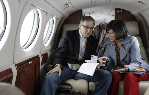 Washington Gov. Jay Inslee, left, is briefed by Dept. of Ecology Director Maia Bellon, right, Wednesday, March 6, 2013, as they fly to Richland, Wash. to tour the Hanford Nuclear Reservation and meet with Dept. of Energy officials in order to learn more about tanks on the site that are leaking radioactive waste. (AP Photo/Ted S. Warren)