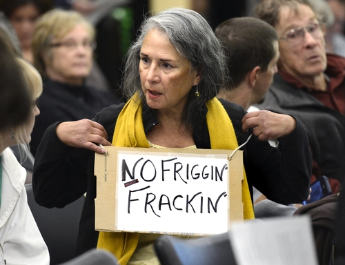 """FILE - In this Dec. 13, 2012 file photo, Elizabeth Allen of Boulder, Colo., wears a """"No Friggin' Frackin"""" sign while waiting for a public meeting to begin on the oil and gas drilling method known as hydraulic fracturing, or """"fracking,"""" at the Boulder County Courthouse in Boulder, Colo. As hydraulic fracturing mobilizes thousands around the country, industry and some environmental groups in Illinois came together to draft regulations both sides could live with. Some hope that cooperative approach could be a model for other states. (AP Photo/Daily Camera, Jeremy Papasso, File)"""