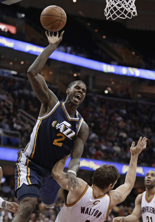 Utah Jazz's Marvin Williams, left, jumps toward the basket against Cleveland Cavaliers' Luke Walton during the fourth quarter of an NBA basketball game Wednesday, March 6, 2013, in Cleveland. Williams was called for an offensive foul. The Cavaliers won 104-101. (AP Photo/Tony Dejak)