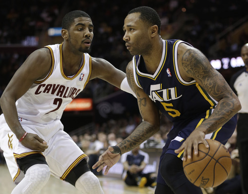 Utah Jazz's Mo Williams (5) works against Cleveland Cavaliers' Kyrie Irving (2) during the fourth quarter of an NBA basketball game Wednesday, March 6, 2013, in Cleveland. The Cavaliers won 104-101. (AP Photo/Tony Dejak)