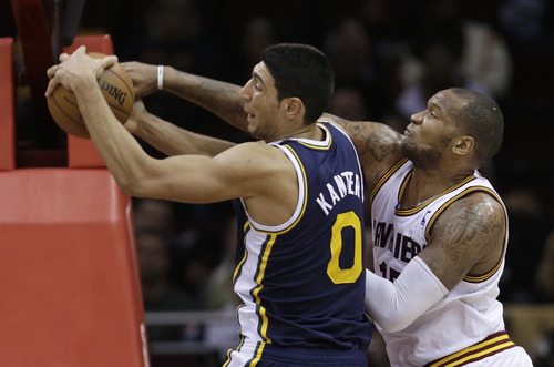 Utah Jazz's Enes Kanter (0), from Turkey, and Cleveland Cavalier's Marreese Speights (15) vie for a rebound during the third quarter of an NBA basketball game Wednesday, March 6, 2013, in Cleveland. The Cavaliers won 104-101. (AP Photo/Tony Dejak)