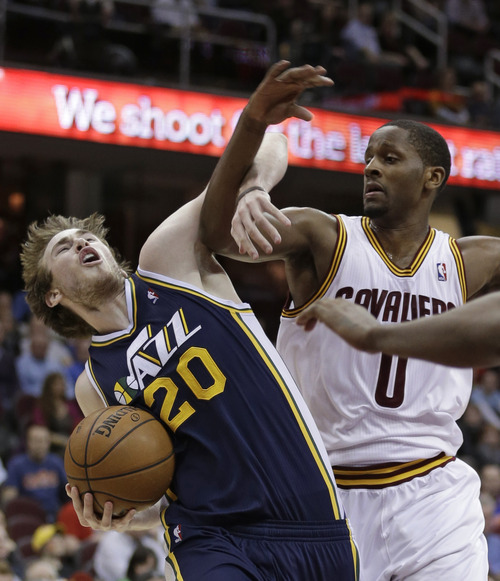 Utah Jazz's Gordon Hayward (20) is fouled by Cleveland Cavaliers' C.J. Miles (0) during the fourth quarter of an NBA basketball game Wednesday, March 6, 2013, in Cleveland. The Cavaliers won 104-101. (AP Photo/Tony Dejak)