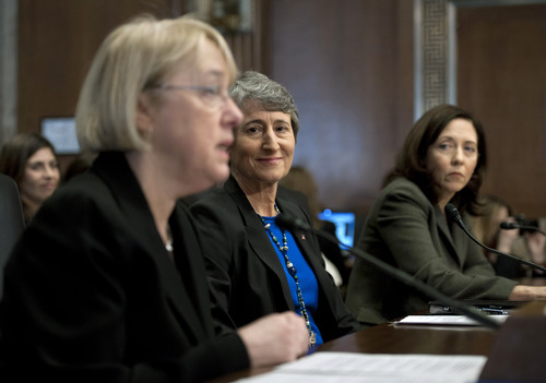 Interior Secretary nominee Sally Jewell, center, flanked Sen. Patty Murray, D-Wash., left, and Sen. Maria Cantwell, D-Wash., listens as Murray introduces her on Capitol Hill in Washington, Thursday, March 7, 2013, during the Senate Energy and Natural Resources Committee hearing on her nomination. (AP Photo/Cliff Owen)