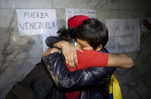 Mexican supporters of Venezuela's President Hugo Chavez embraces in front of Venezuela's embassy in Mexico City, Tuesday, March 5, 2013. Venezuela's Vice President Nicolas Maduro announced that Chavez died on Tuesday at age 58 after a nearly two-year bout with cancer. (AP Photo/Eduardo Verdugo)