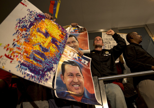 Supporters of Venezuela's President Hugo Chavez holds up images depicting him outside the Venezuelan embassy in Buenos Aires, Argentina, Tuesday, March 5, 2013. Venezuela's Vice President Nicolas Maduro announced that Chavez died on Tuesday at age 58 after a nearly two-year bout with cancer. (AP Photo/Victor R. Caivano)