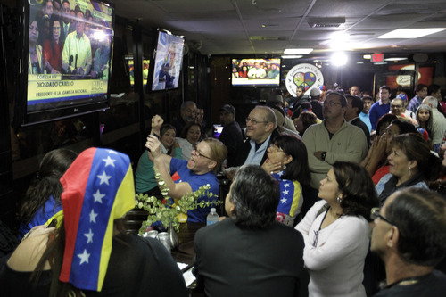 A crowd gathers at the Arepazo 2 restaurant in Doral, Fla., Tuesday, March 5, 2013, after hearing the news of Venezuelan president Hugo Chavez's death. (AP Photo/Luis M. Alvarez)