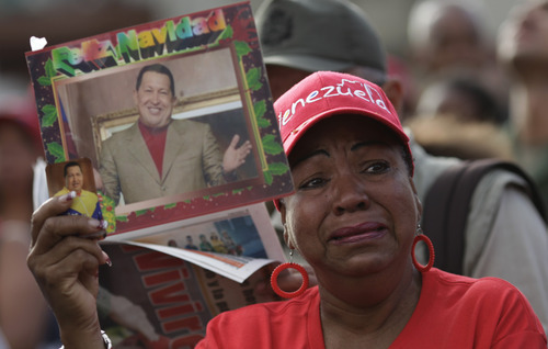 A woman holds a picture of President Hugo Chavez  outside the military hospital where he died Tuesday in Caracas, Venezuela, Wednesday, March 6, 2013.  Seven days of mourning were declared, all school was suspended for the week and friendly heads of state were expected  for an elaborate funeral Friday..(AP Photo/Ariana Cubillos)