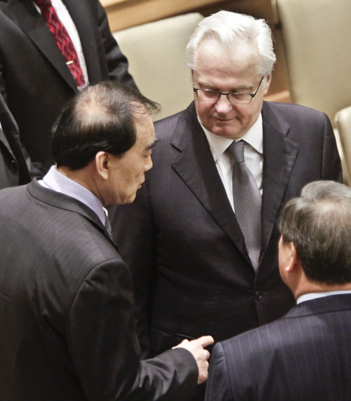Russia's UN Ambassador Vitaly Churkin, center, current president for the U.N. Security Council, listens as he confers with China's UN Ambassador Li Baodong, left, before leading council members on a vote for tough new sanctions against North Korea for its latest nuclear test, during a meeting at U.N. headquarters Thursday, March 7, 2013. The unanimous vote by the U.N.'s most powerful body sparked a furious Pyongyang to threaten a nuclear strike against the United States. (AP Photo/Bebeto Matthews)