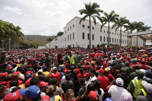 A crowd waits to enter the military academy where the body of Venezuela's late President Hugo Chavez lies in state in Caracas, Venezuela, Thursday, March 7, 2013. While Venezuela remains deeply divided over the country's future, the multitudes who reached the president's coffin early Thursday were united in grief and admiration for a man many considered a father figure.   (AP Photo/Ariana Cubillos)