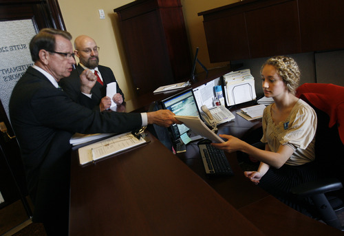 Scott Sommerdorf   |  The Salt Lake Tribune Lieutenant Governor's Office administrative assistant Laurie Decker accepts a petition from David Irvine as his attorney, Alan Smith, second from left, looks on Thursday. The petition seeks an investigation into Attorney General John Swallow's election activities and seeks statutory remedies for any violations found.