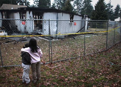 Rick Egan  | The Salt Lake Tribune   Two young girls hug as they look at the home where Josh Powell took his life and the lives of Charlie and Braden, in Graham, Wash., Wednesday, February 8, 2012.