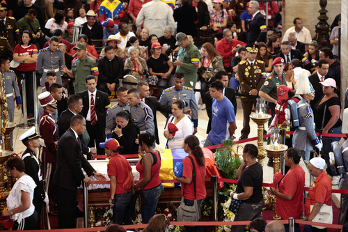 In this photo released by Miraflores Press Office,  mourners walk beside the coffin  containing the body of  Venezuela's late President Hugo Chavez on display during his wake at a military academy where his body will lie in state until his funeral in in state in Caracas, Venezuela, Thursday, March 7, 2013.  While Venezuela remains deeply divided over the country's future, the multitudes who reached the president's coffin were united in grief and admiration for a man many considered a father figure. Chavez died on March 5 after a nearly two-year bout with cancer.(AP Photo/Miraflores Press Office)
