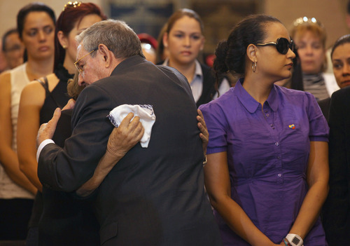 In this photo released by Miraflores Press Office,  Cuba's President Raul Castro embraces an unidentified mourner next to the coffin containing the remains of  Venezuela's late President Hugo Chavez during his wake at a military academy where his body will lie in state until his funeral in in state in Caracas, Venezuela, Thursday, March 7, 2013.  Nicolas Maduro, Venezuela's acting president, said Chavez's  remains will be put on permanent display at the Museum of the Revolution, close to the presidential palace where Chavez ruled for 14 years. A state funeral for Chavez attended by some 33 heads of government is scheduled to begin Friday morning.  At right is Chavez's daughter Rosa Virginia Chavez.(AP Photo/Miraflores Press Office)
