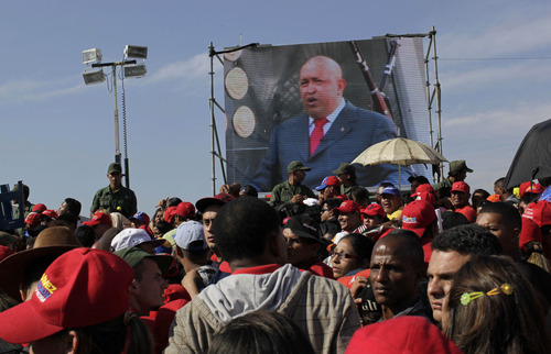 A screen showing a video image of Venezuela's President Hugo Chavez plays in front of the site where Chavez's funeral ceremony will take place as people gather outside the military academy in Caracas, Venezuela, Friday, March 8, 2013.  Friday's funeral promises to be a final turn on the world stage for Chavez after 14 years in power, though in some ways the former paratrooper is not going anywhere: Venezuela announced Thursday that it would embalm his body and put it on permanent display. Chavez died on March 5 after a nearly two-year bout with cancer.  He was 58. (AP Photo/Rodrigo Abd)