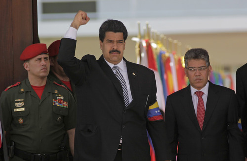Venezuela's Vice President Nicolas Maduro raises his fist as he arrives along with Foreign Minister Elias Jaua, right, for the funeral ceremony for Venezuela's late President Hugo Chavez at the military academy in Caracas, Venezuela, Friday, March 8, 2013. With leaders from five continents on hand, Venezuela prepared for a day of distinctly different ceremonies, first the formal state funeral of Hugo Chavez, then the controversial swearing in of Maduro, his anointed interim successor, who the opposition charges has no constitutional right to the job. (AP Photo/Rodrigo Abd)