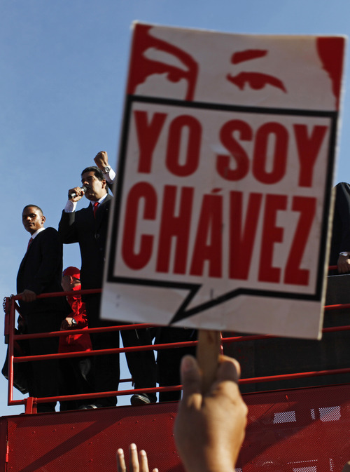 "A supporter of Venezuela's late President Hugo Chavez holds up a sign that says in Spanish ""I am Chavez"" as Vice President Nicolas Maduro speaks to the crowd outside the military academy where Chavez's body is lying in state in Caracas, Venezuela, Thursday, March 7, 2013.  Maduro, Venezuela's acting president, said Chavez's remains will be put on permanent display at the Museum of the Revolution, close to the presidential palace where Chavez ruled for 14 years. A state funeral for Chavez attended by some 33 heads of government is scheduled to begin Friday morning. Chavez died on March 5 after a nearly two-year bout with cancer.  He was 58.  (AP Photo/Rodrigo Abd)"