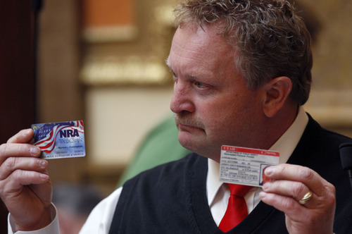 Al Hartmann  |  The Salt Lake Tribune Rep. Rich Cunningham, R-South Jordan holds up his NRA card and Utah concealed carry permit during debate on 2HB 114 Second Amendment Preservation Act Friday March 8 in the Utah House of Representatives.
