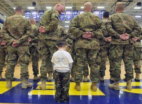 3-year-old Seth Byers looks at his father Chief Warrant Officer 3 Todd King, for the first time as more than 160 local soldiers from the 507th Engineer Battalion returned home during a homecoming event at Portage, Mich. Central High School's gymnasium, Saturday, March 9, 2013 after a 10-month deployment in Afghanistan. (AP Photo/Kalamazoo Gazette-MLive Media Group, Matt Gade) ALL LOCAL TV OUT; LOCAL TV INTERNET OUT