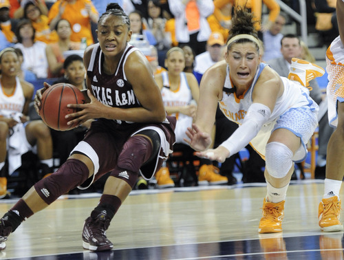 Texas A&M guard Courtney Walker (33) gets by a diving Tennessee guard Taber Spani (13) during the first half of a NCAA college basketball game in the Southeastern Conference tournament, Saturday, March 9, 2013, in Duluth, Ga. (AP Photo/John Amis)