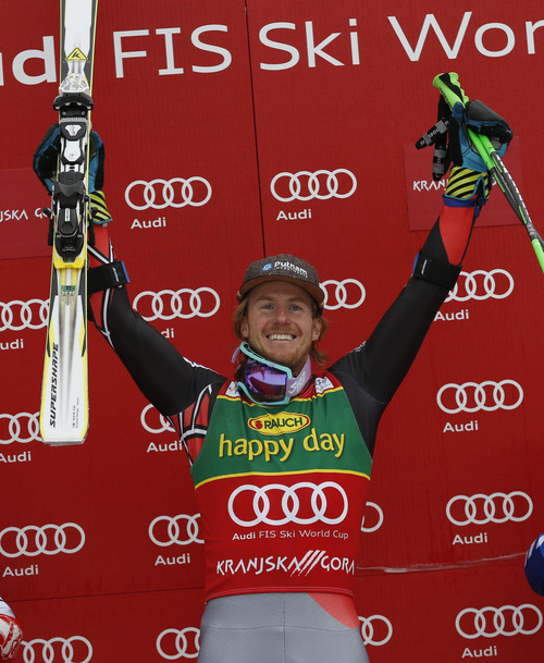 Ted Ligety, of the United States, celebrates on the podium after winning an alpine ski, men's World Cup giant slalom, in Kranjska Gora, Slovenia, Saturday, March 9, 2013. (AP Photo/Alessandro Trovati)