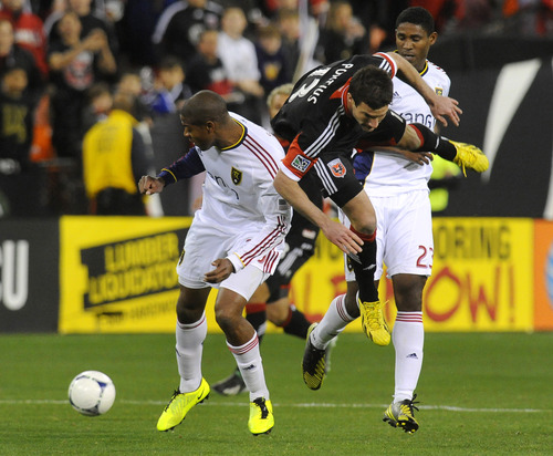 Real Salt Lake defender Chris Schuler (left) makes contact with DC United forward Chris Pontius (13) as he bumps him off the ball during first half of their MLS soccer game, Saturday, March 9, 2013, in Washington. (AP Photo/Richard Lipski)