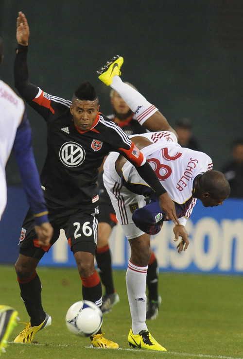 Real Salt Lake defender Chris Schuler takes a tumble as D.C. United forward Lionard Pajoy (26) maintains control of the ball during first half of an MLS soccer game, Saturday, March 9, 2013, in Washington. United defeated Real Salt Lake 1-0. (AP Photo/Richard Lipski)