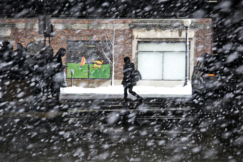 A woman makes her way across the bus station in downtown New Bedford, Mass., as heavy snow falls Friday, March 8, 2013. The storm dropped up to a foot of snow in some parts of New England, caused coastal flooding in Massachusetts. (AP Photo/The Standard-Times, Peter Pereira)