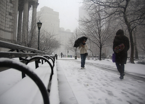 People walk through driving snow near courthouses in lower Manhattan during a storm on Friday, March. 8 2013, in New York. A very wet snow is causing slippery road conditions in the metropolitan area and several inches have fallen on eastern Long Island and Westchester, Rockland and Putnam counties.(AP Photo/Peter Morgan)