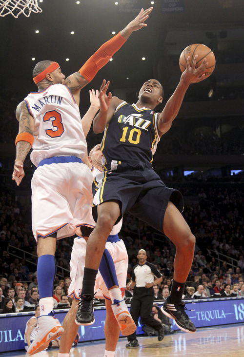Utah Jazz's Alec Burks (10) goes up against New York Knicks Kenyon Martin during the first half of an NBA basketball game on Saturday, March 9, 2013, at Madison Square Garden in New York. (AP Photo/Mary Altaffer)
